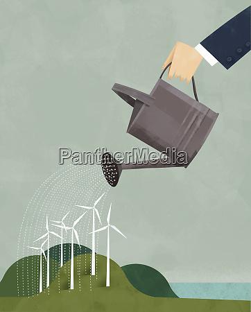 businessman watering wind turbines