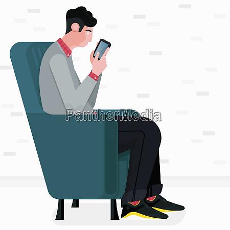 man sitting in armchair using smart