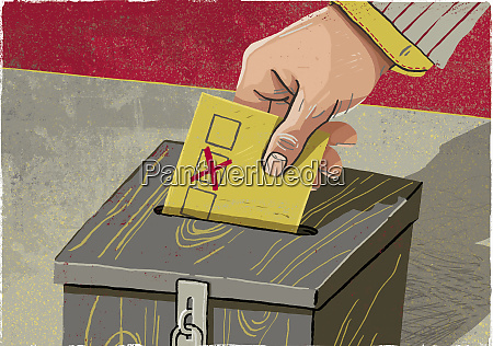 hand depositing voting paper in ballot