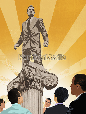 colleagues admiring businessman standing on top