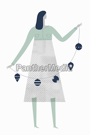 woman holding string of christmas baubles