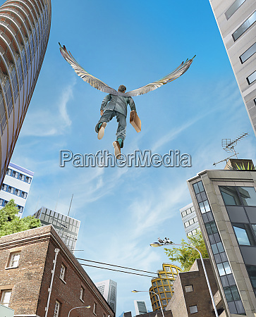 successful businessman with wings flying over
