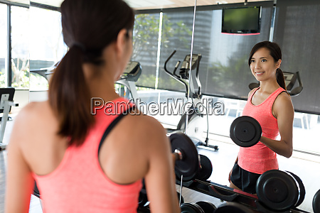 young woman practices weight lifting of