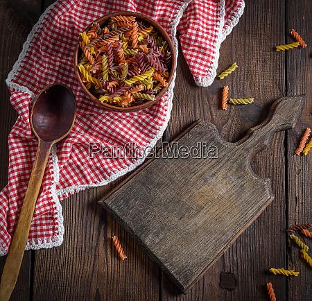 raw pasta fusilli on a brown