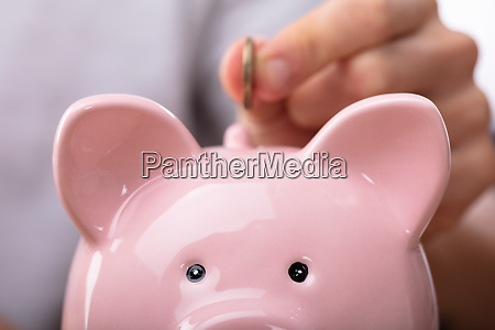 person inserting coin in piggybank