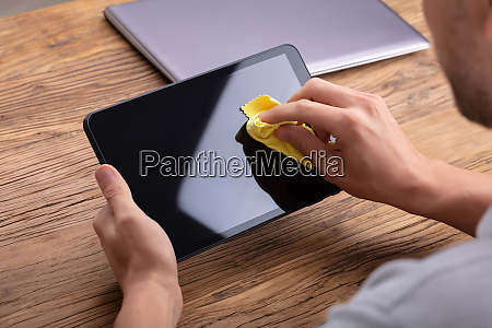 mans hand cleaning digital tablet screen