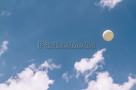 white balloon flying in a perfect