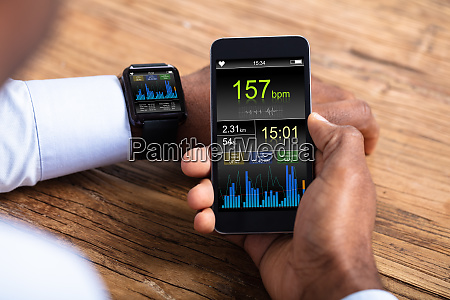 man with smartwatch and cellphone monitoring