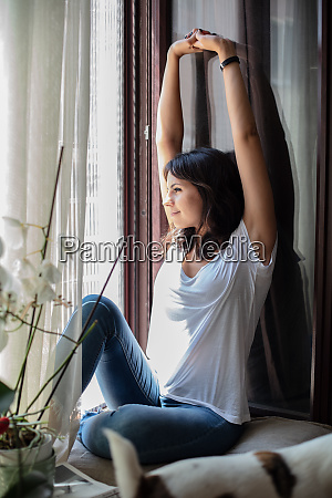 relaxed contented young woman stretching her