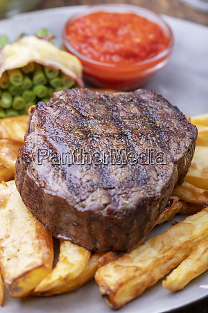 closeup of grilled steak with french