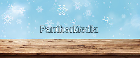 blue snowflakes background with wooden table