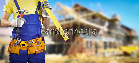 worker with tool belt in house