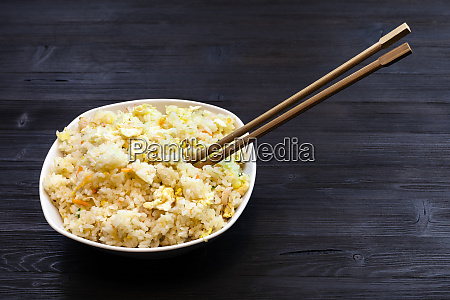 bowl with fried rice with chopsticks