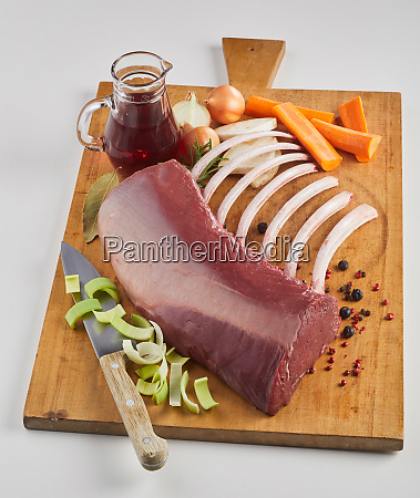 raw meat and vegetables on cutting