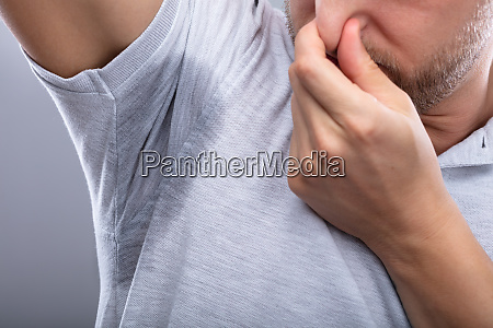 man with sweaty armpit covering his