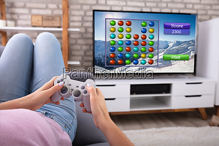 woman playing video game on television