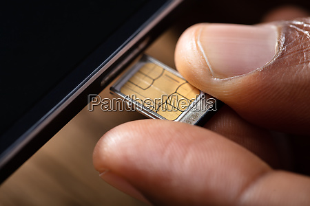 person inserting sim card in cellphone