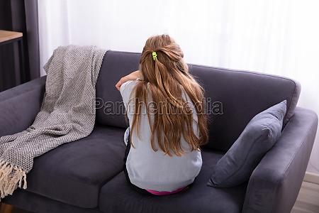 sad girl sitting on sofa