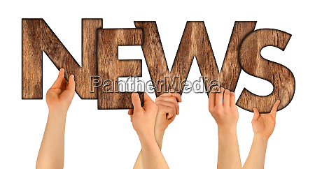 news people holding up wooden letters