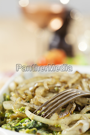 closeup of bavarian kaesspaetzle dangling from