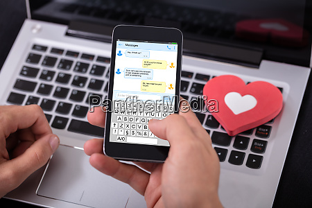 man sending text message on mobile