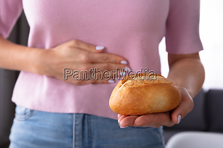 woman having stomach pain holding bread
