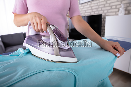 woman ironing t shirt with electric
