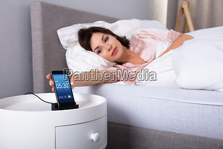 woman snoozing alarm on mobile phone
