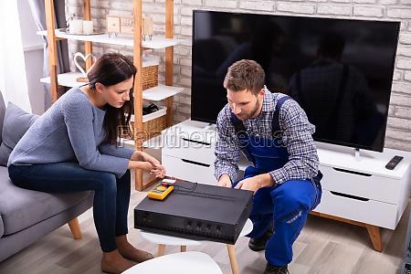 woman sitting near technician repairing amplifier