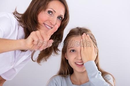 optometrist assisting girl while checking eyesight