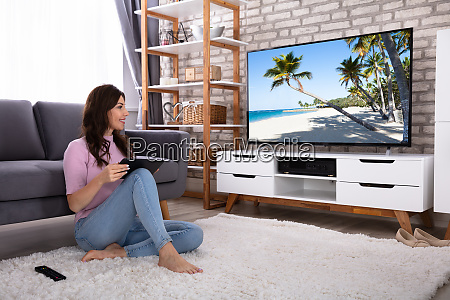happy young woman watching television