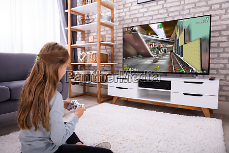 girl playing video game on television