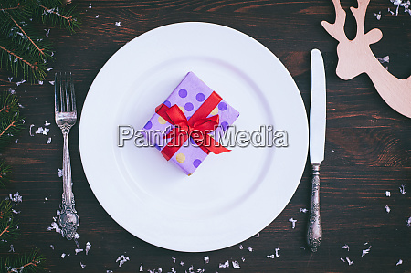packed gift on white empty plate