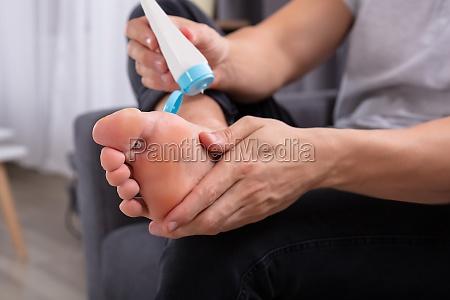 man applying cream on his feet
