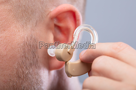 man putting hearing aid in his