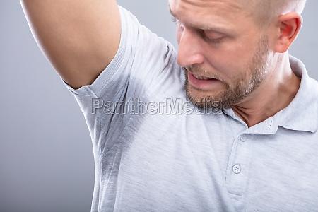 man sweating badly under armpit