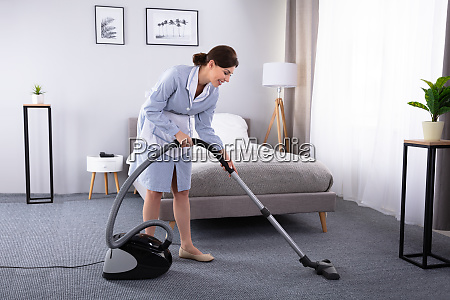 housekeeper cleaning carpet with vacuum cleaner