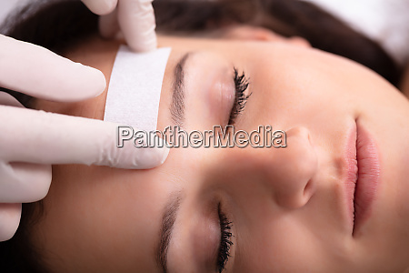 doctor waxing womans forehead