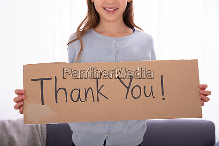 girl holding cardboard with thank you