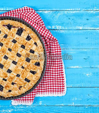 half of fruit pie on blue
