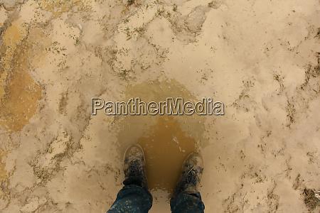 man standing in mud