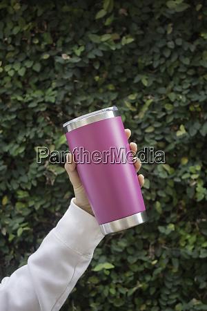 hand on stainless steel tumbler mug