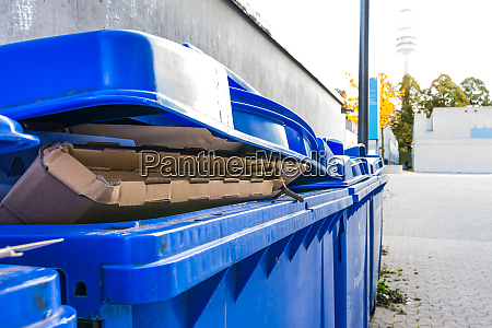 overflowing paper recycling storage bin dumpster