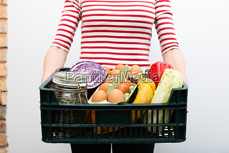 woman holding box of grocery food