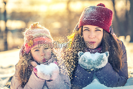 mother and daughter playing in winter