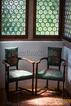 two vintage chairs near a window