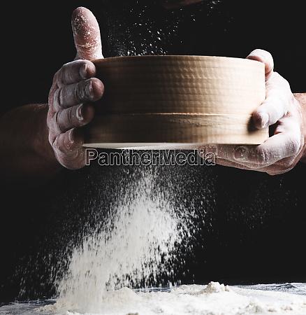 round wooden sieve with flour in