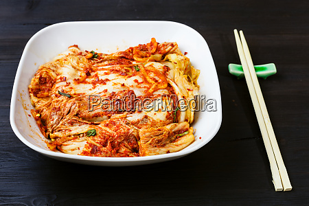 kimchi in white bowl and chopsticks
