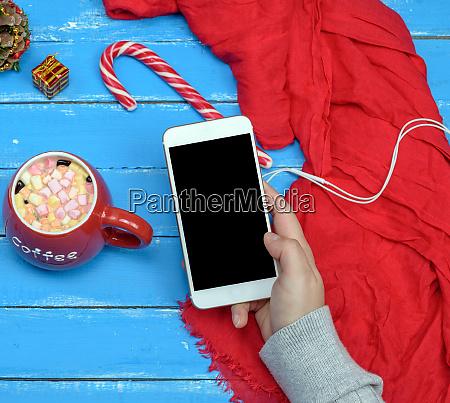 female hand holding white smart phone