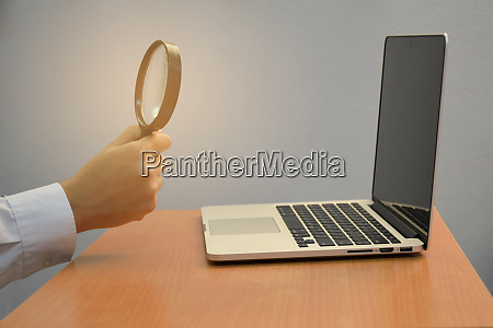 business male hand holding magnifying glass